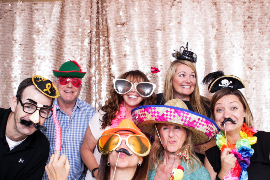 Group of friends in props enjoying the Santa Monica photo booth