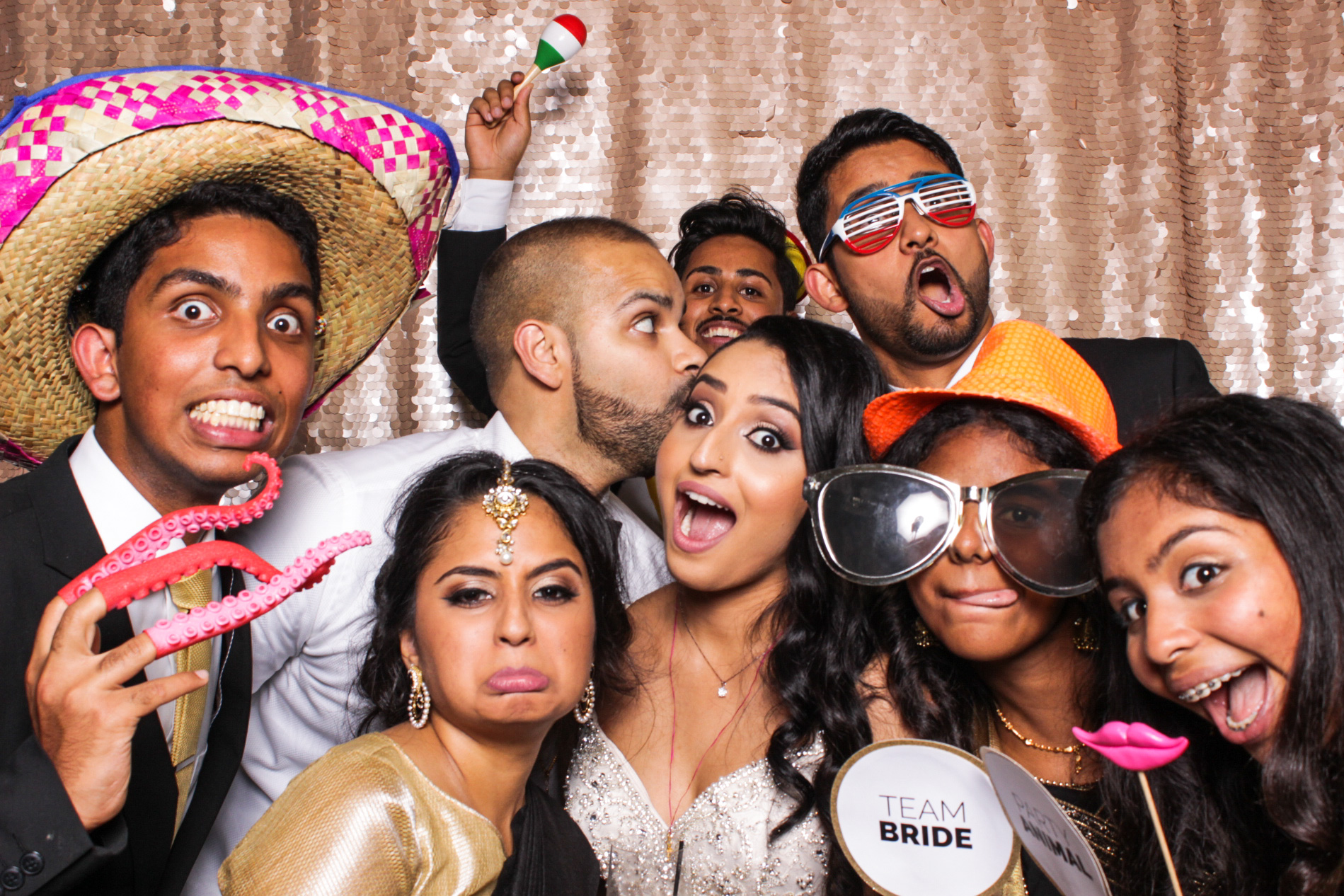 A bride being kissed by the groom surrounded by friends pulling fun faces with props in the pasadena photo booth
